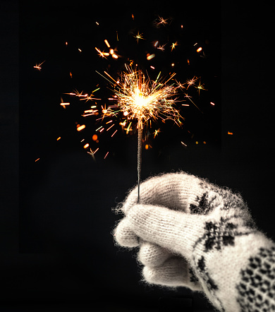 Festive Merry Christmas sparklers. Golden Magic lights for holiday poster, birthday or party concept. Hand, holding Sparkling beautiful sparkles or  bengal lights