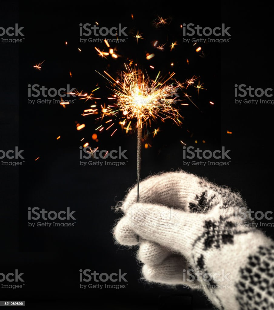 Festive Merry Christmas sparklers. Golden Magic lights for holiday poster, birthday or party concept. Hand, holding Sparkling beautiful sparkles or  bengal lights stock photo