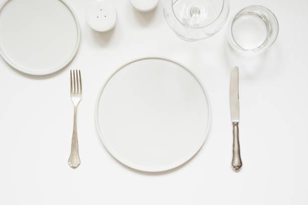 festliche moderne weiße tischdekoration. teller und besteck auf weiß. ansicht von oben. - menüplanung vorlagen stock-fotos und bilder
