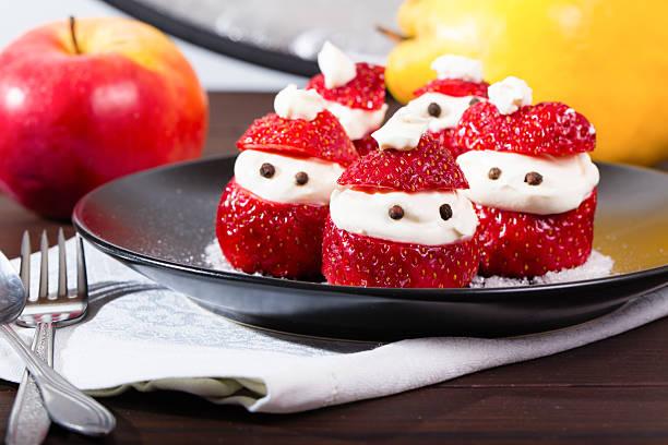 festive new year's strawberry dessert - weihnachtsmannhüte aus erdbeeren stock-fotos und bilder
