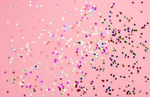 istock Festive pastel pink background with metallic confetti. 1050979248