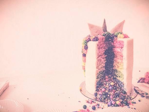 festliche regenbogen einhorn kuchen rosa hintergrund w/copy space - brautparty kuchen stock-fotos und bilder