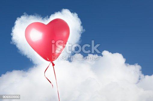 istock festive red heart balloon on blue sky 909303930