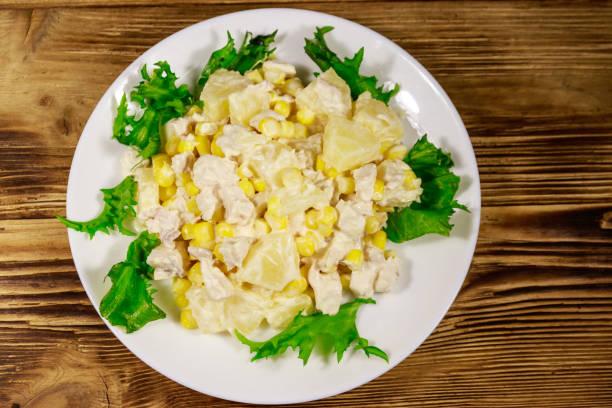 festlicher salat mit hühnerbrust, süßem mais, ananas und mayonnaise auf holztisch - ananas huhn salate stock-fotos und bilder
