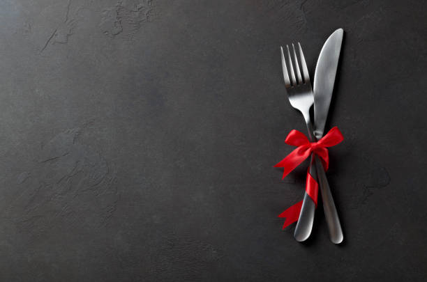 Festive set of cutlery knife and fork with red satin bow, dark s stock photo