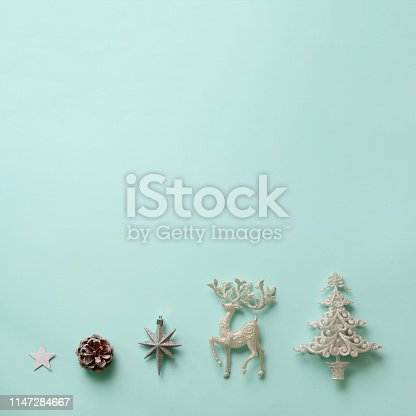 istock Festive silver deer, stars, fir-tree, cone on blue background with copy space. Square crop. Christmas and new year party. Minimal concept. Flat lay, top view 1147284667