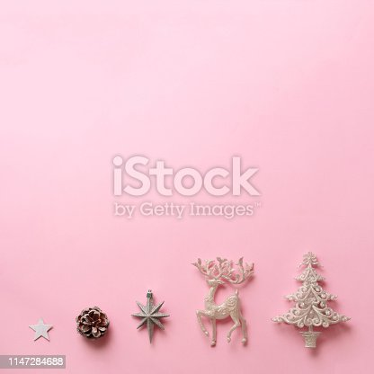 istock Festive silver deer, stars, fir-tree, cone on pink background with copy space. Square crop. Christmas and new year party. Minimal concept. Flat lay, top view 1147284688