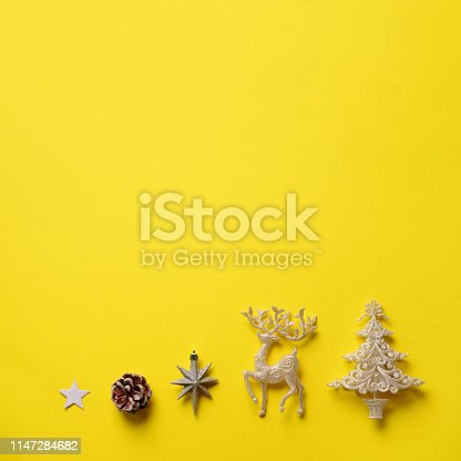 istock Festive silver deer, stars, fir-tree, cone on yellow background with copy space. Square crop. Christmas and new year party. Minimal concept. Flat lay, top view 1147284682