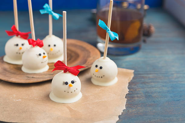 festive snowman cake pops against blue background. - lutscher cookies stock-fotos und bilder