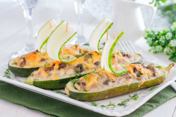 festlich, gefüllt mit fleisch und pilzen zucchini in form von booten, dekoriert mit frischen gurken, horizontale - gefüllte zucchini vegetarisch stock-fotos und bilder