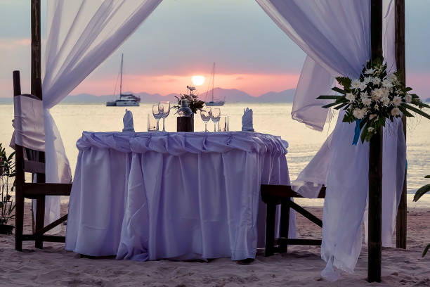 Festive table by the sea. Decorated for a romantic dinner. Against the backdrop of sunset, yachts and mountains. Festive table by the sea. Decorated for a romantic dinner. Against the backdrop of sunset, yachts and mountains. indochina stock pictures, royalty-free photos & images