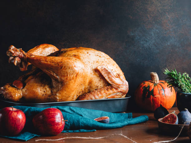 Festive table for Thanksgiving Holiday with whole roasted turkey with apple, pumpkin, figs and herbs in a mortar. stock photo