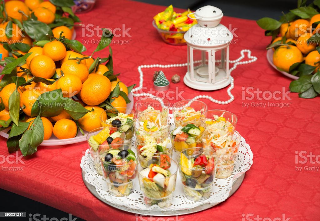 Festive table: fruits (tangerines), snacks, salads, sweets, Christmas decorations stock photo
