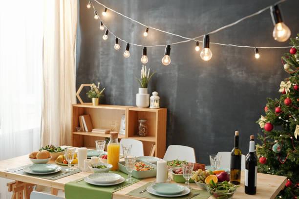 Festlicher Tisch für Weihnachtsfeier mit Lampen hängen über Mahlzeit serviert – Foto