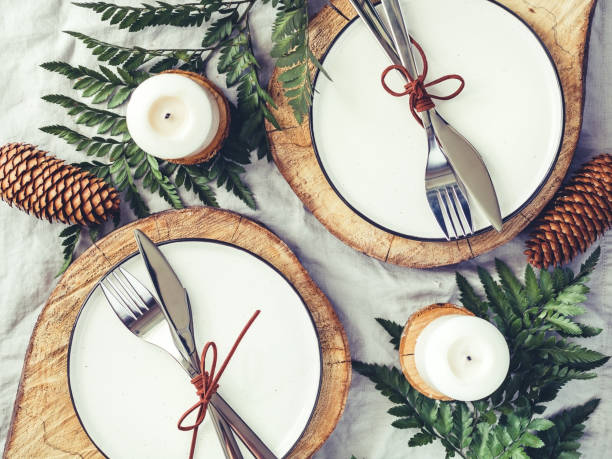 Festive table setting among winter decorations and white candles. Top view, flat lay. The concept of a Christmas or Thanksgiving family dinner. stock photo