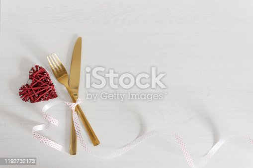 istock Festive table setting for Valentine's Day with golden fork and knife and holiday decorations. 1192732173