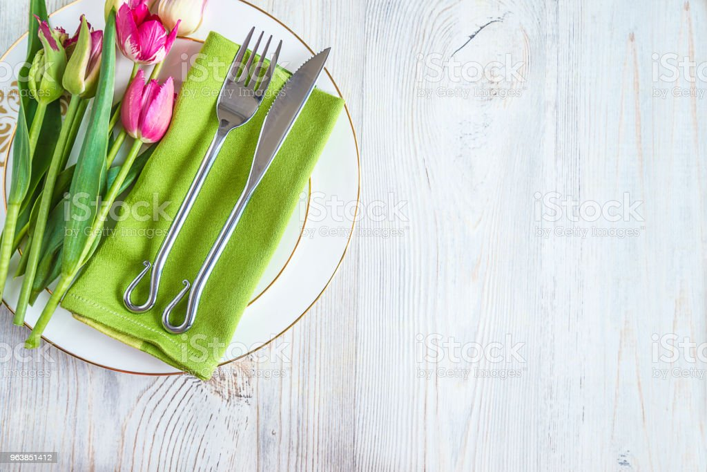 Festive table setting with original cutlery on green napkin and bouquet of tulips in napkin ring on white wooden background with copy space - Royalty-free Anniversary Stock Photo