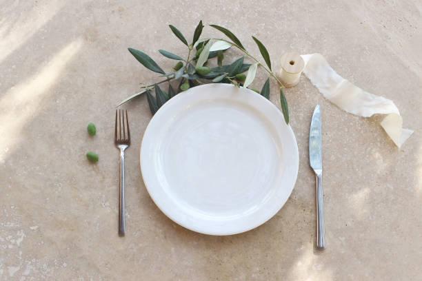 festliche tisch sommer-einstellung mit silber besteck, olivenzweig, porzellanplatte und seidenband. auf marmor hintergrund im sonnenlicht. mediterrane hochzeit oder restaurant menükonzept. flachliegen, ansicht von oben - tischdeko goldene hochzeit stock-fotos und bilder