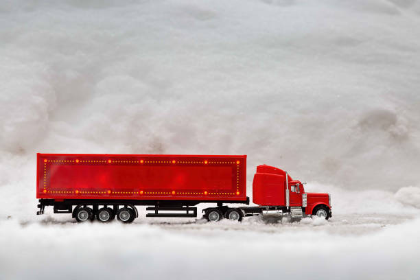 Festive truck in red. toy car rides on the background of real snowdrifts. Winter. Christmas holidays. stock photo