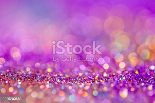 992937254 istock photo Festive twinkle glitters background, abstract glowing backdrop with circles,modern design overlay with sparkling glimmers. Pink, purple and golden backdrop glittering sparks with blur effect. 1249200632