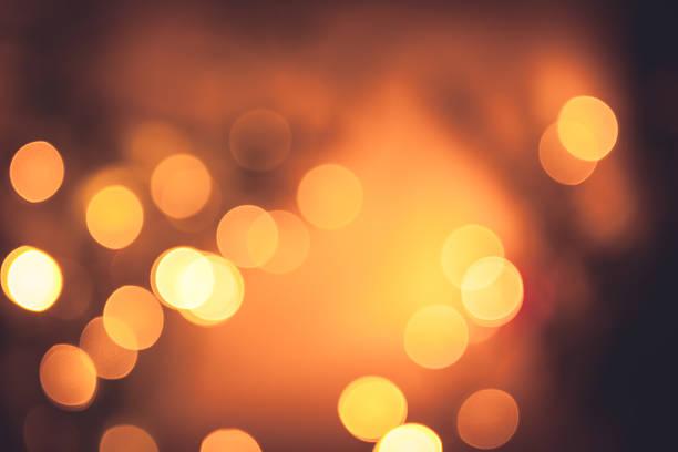festive warm bokeh with sparkling christmas lights in orange colors - luz da vela - fotografias e filmes do acervo
