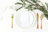 Festive wedding, birthday table setting with golden cutlery, eucalyptus parvifolia branch, porcelain plate, milk and silk ribbon. Blank card mockup. Rustic restaurant menu concept, flat lay, top view