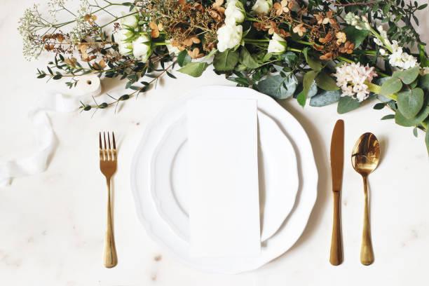 festliche hochzeit, geburtstagstisch-einstellung mit goldenem besteck, seidenband, eukalyptuszweige, hortensien und weiße rosen blumen. blanke karte mockup. restaurant-menü-konzept. flache, obere ansicht - tischdeko goldene hochzeit stock-fotos und bilder