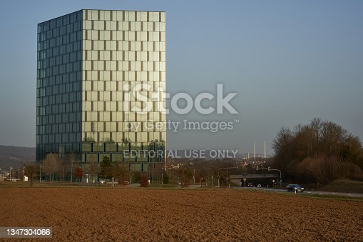 istock Festo automation Center. Office building with blue glass facade at at evening light. Brown agricultural field. Road with cars. Europe, Berkheim, Zollberg. 1347304066