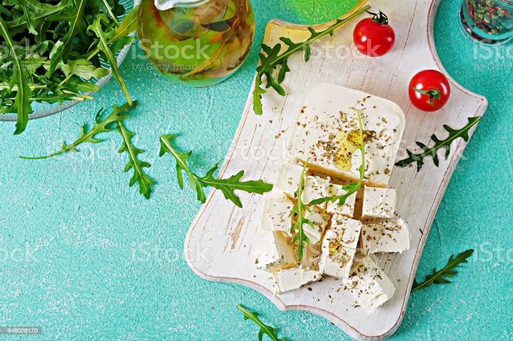 Feta-Käse, Cherry-Tomaten und Rucola auf den Tisch. Zutaten für Salat. Ansicht von oben – Foto