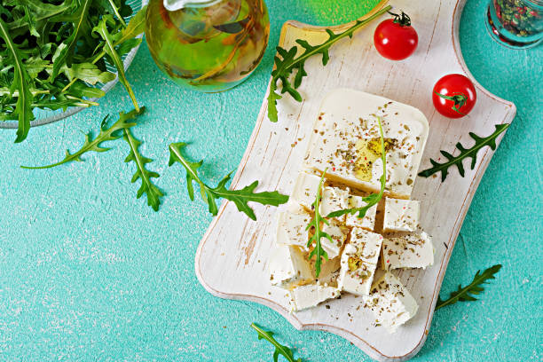 Feta cheese, cherry tomatoes and rucola on the table. Ingredients for salad. Top view Feta cheese, cherry tomatoes and rucola on the table. Ingredients for salad. Top view feta cheese stock pictures, royalty-free photos & images