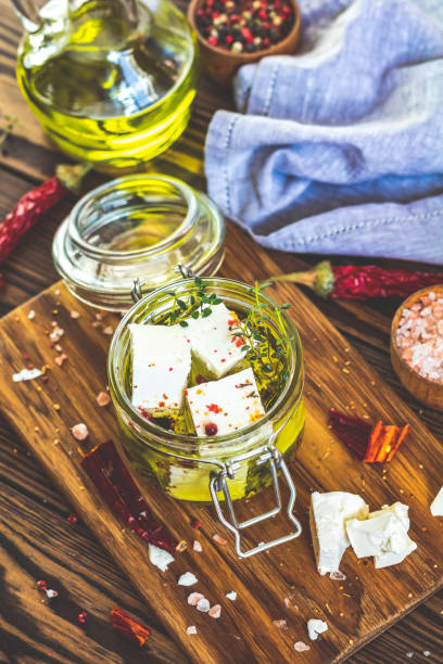 Feta cheese marinated in olive oil in glass jar stock photo