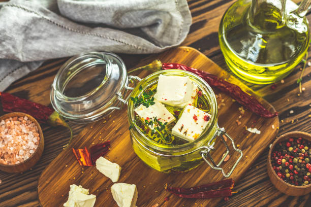 Feta cheese marinated in olive oil with fresh herbs in glass jar stock photo