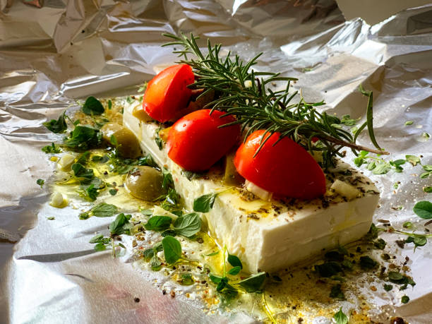Feta cheese on aluminum foil with rosemary, garlic,olives, thyme and tomatoes stock photo