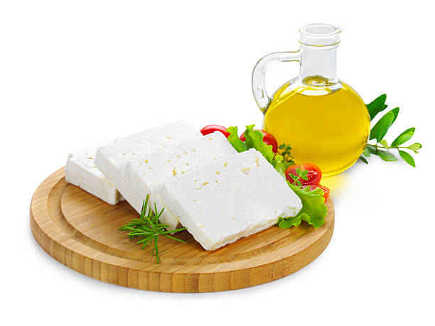 feta cheese slices on wood feta cheese(Greek cheese) slices on a wooden serving board decorated with fresh vegetables and a bottle of olive oil feta cheese stock pictures, royalty-free photos & images