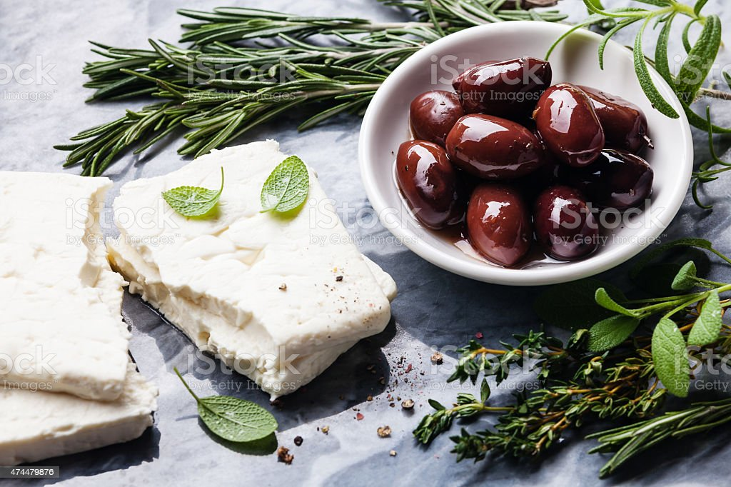 Feta cheese with olives and green herbs stock photo