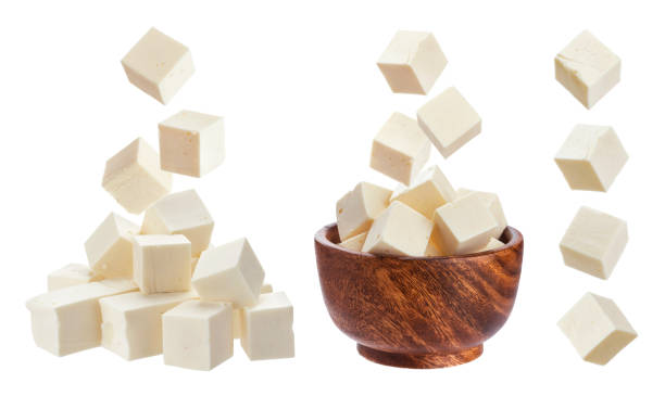 Feta isolated. Falling pieces of white cheese Greek feta cubes. Diced soft cheese isolated on white background with clipping path feta cheese stock pictures, royalty-free photos & images