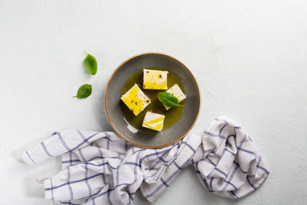Feta with olive oil and spice in bowl on light surface stock photo