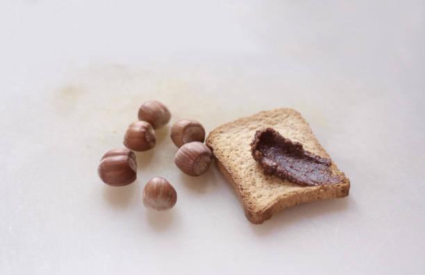 fetta biscottata con crema di nocciole - fette biscottate foto e immagini stock