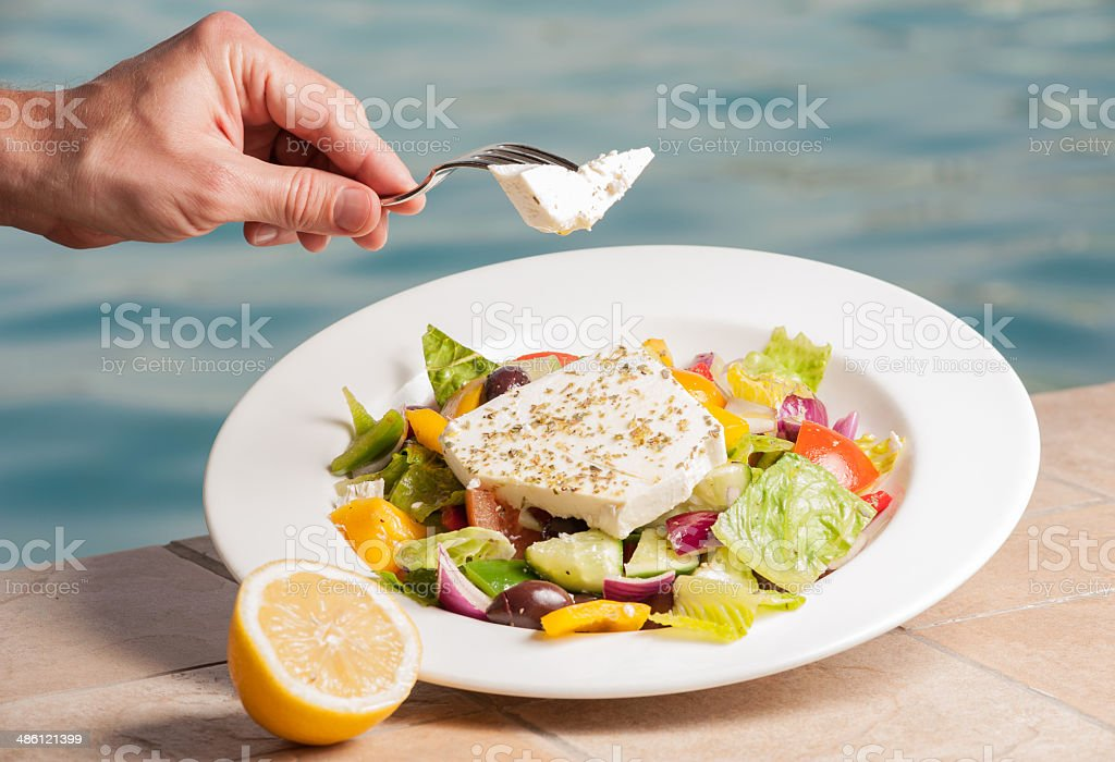 Fetta salad withhand and fork stock photo
