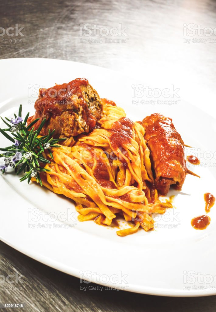 Fettuccine all'abruzzese: rich tasty homemade fresh pasta plate with meat rolls, bacon, and tomato sauce stock photo