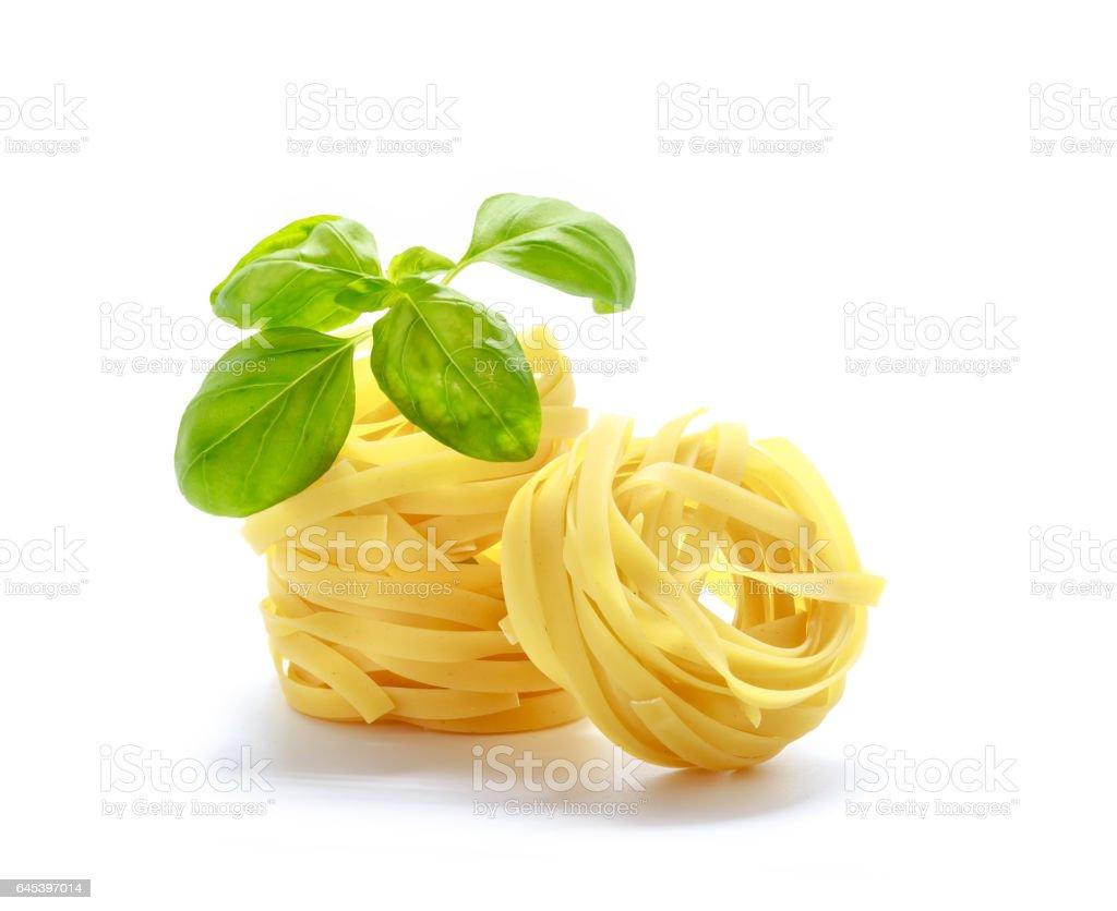 Fettuccine italian pasta with basil isolated on white background stock photo