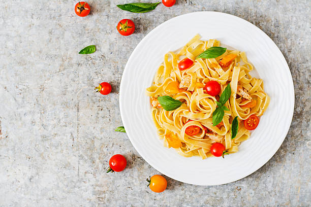 Fettuccine pasta in tomato sauce with chicken, tomatoes Fettuccine pasta in tomato sauce with chicken, tomatoes decorated with basil on a table. Top view tagliatelle stock pictures, royalty-free photos & images