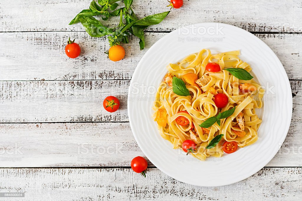 Fettuccine pasta in tomato sauce with chicken, tomatoes stock photo