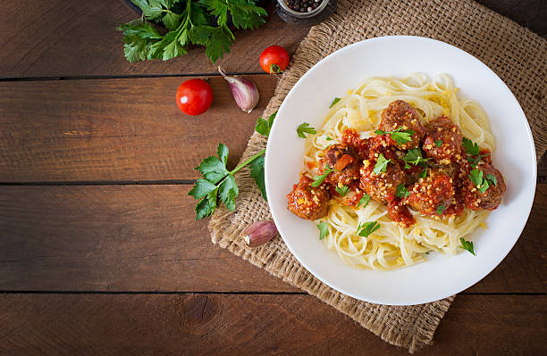 fettuccine pasta with meatballs in tomato sauce - italian food stock photos and pictures