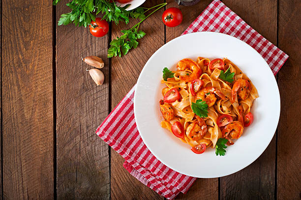 Fettuccine pasta with shrimp, tomatoes and herbs Fettuccine pasta with shrimp, tomatoes and herbs macaroni stock pictures, royalty-free photos & images