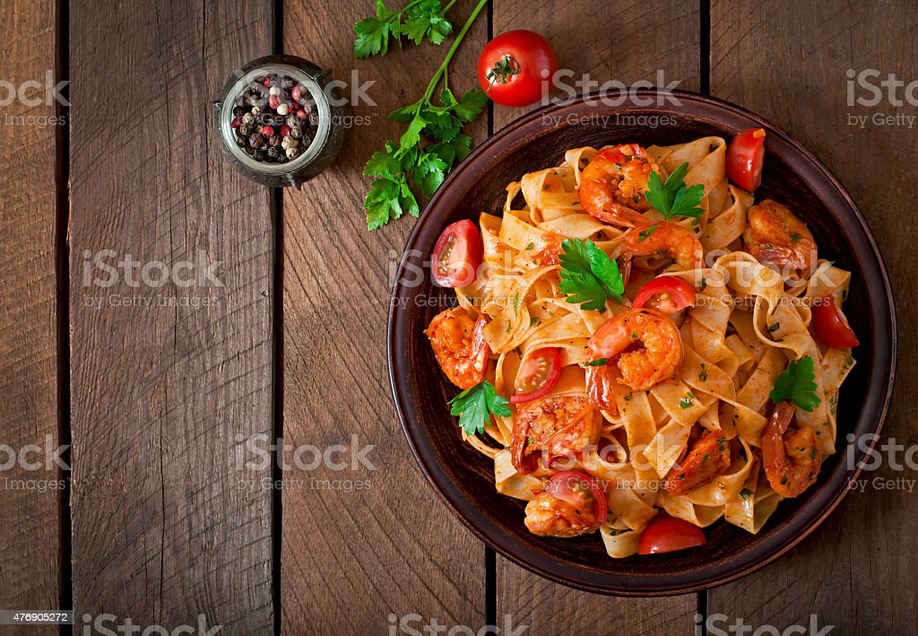 Fettuccine pasta with shrimp, tomatoes and herbs stock photo
