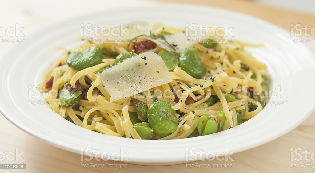 Fettuccine with parmesan, broad bean and tomatoes. stock photo