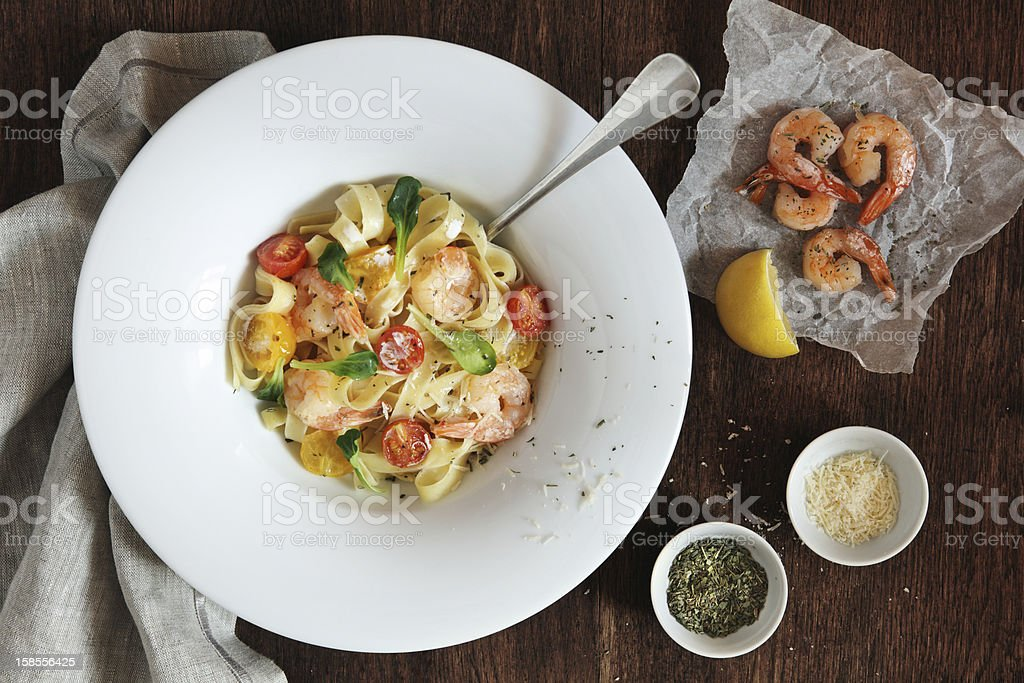 Fettuccine with shrimps, cherry tomatoes and cheese stock photo