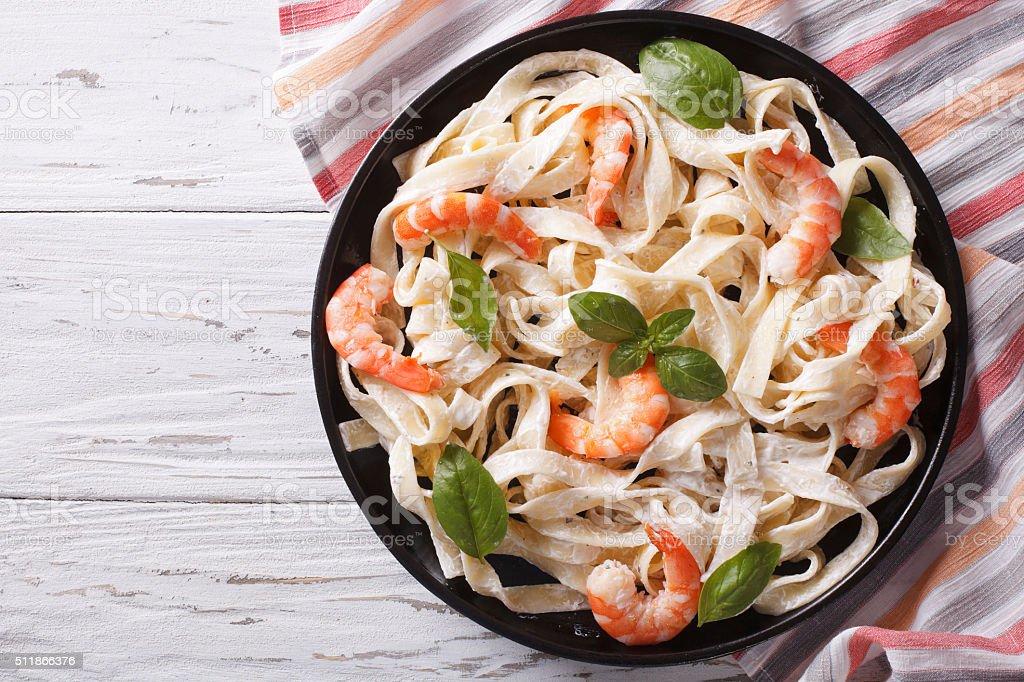 fettuccini pasta in cream sauce with shrimp. horizontal top view stock photo