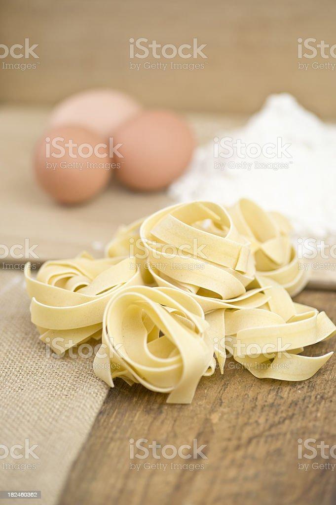 Fettucini pasta, eggs, flour on wood and sack cloth royalty-free stock photo